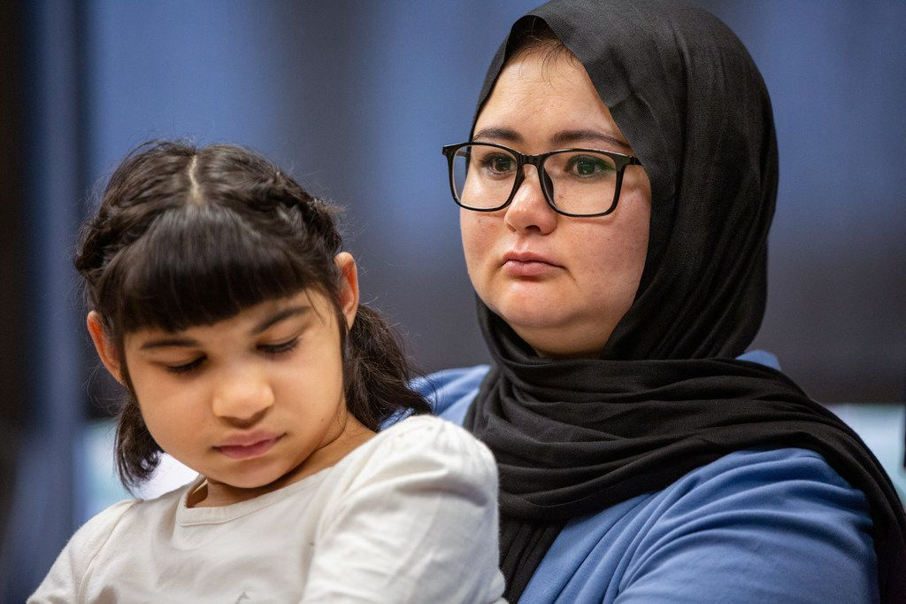 Zahra Amiri, right, the wife of security officer Mahir Ahmad Amiri, holds her daughter Zianib, 8, as she listens to reporters during a press conference in North Dallas on Monday.