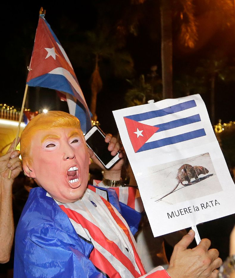 "A person wearing a Donald Trump mask holds a sign in Spanish that reads ""the rat dies"" in Miami's Little Havana area early Saturday. (AP Photo/Alan Diaz)"