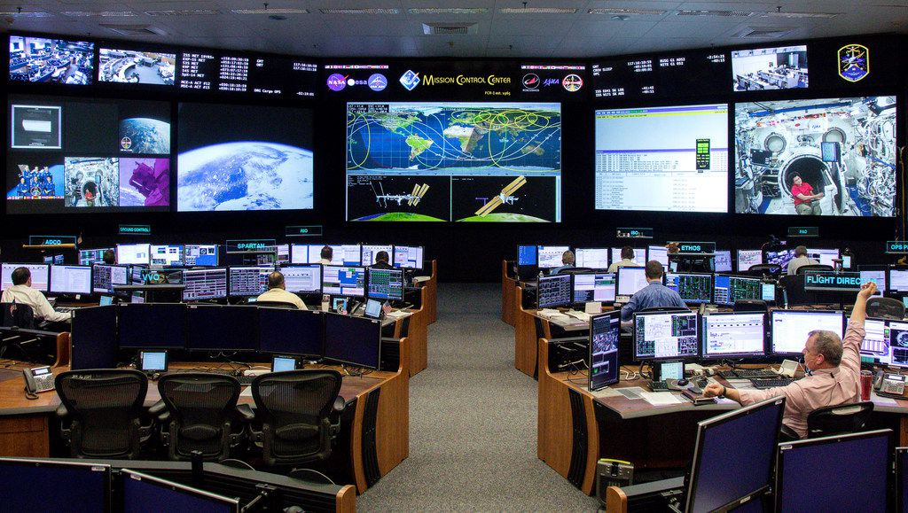 """Timothy """"T.J."""" Creamer, right, a former astronaut and current mission control flight director at NASA, works in the mission control room at Johnson Space Center in Houston."""