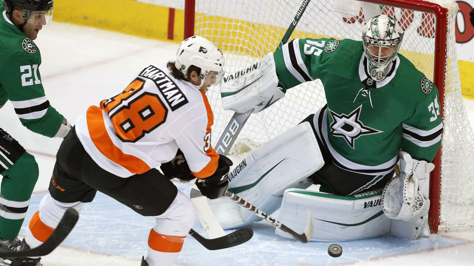 Philadelphia Flyers right wing Ryan Hartman (38) attacks the goal against Dallas Stars defenseman Ben Lovejoy (21) and goaltender Anton Khudobin (35) during the first period of an NHL hockey game in Dallas, Tuesday, April 2, 2019. (AP Photo/LM Otero)