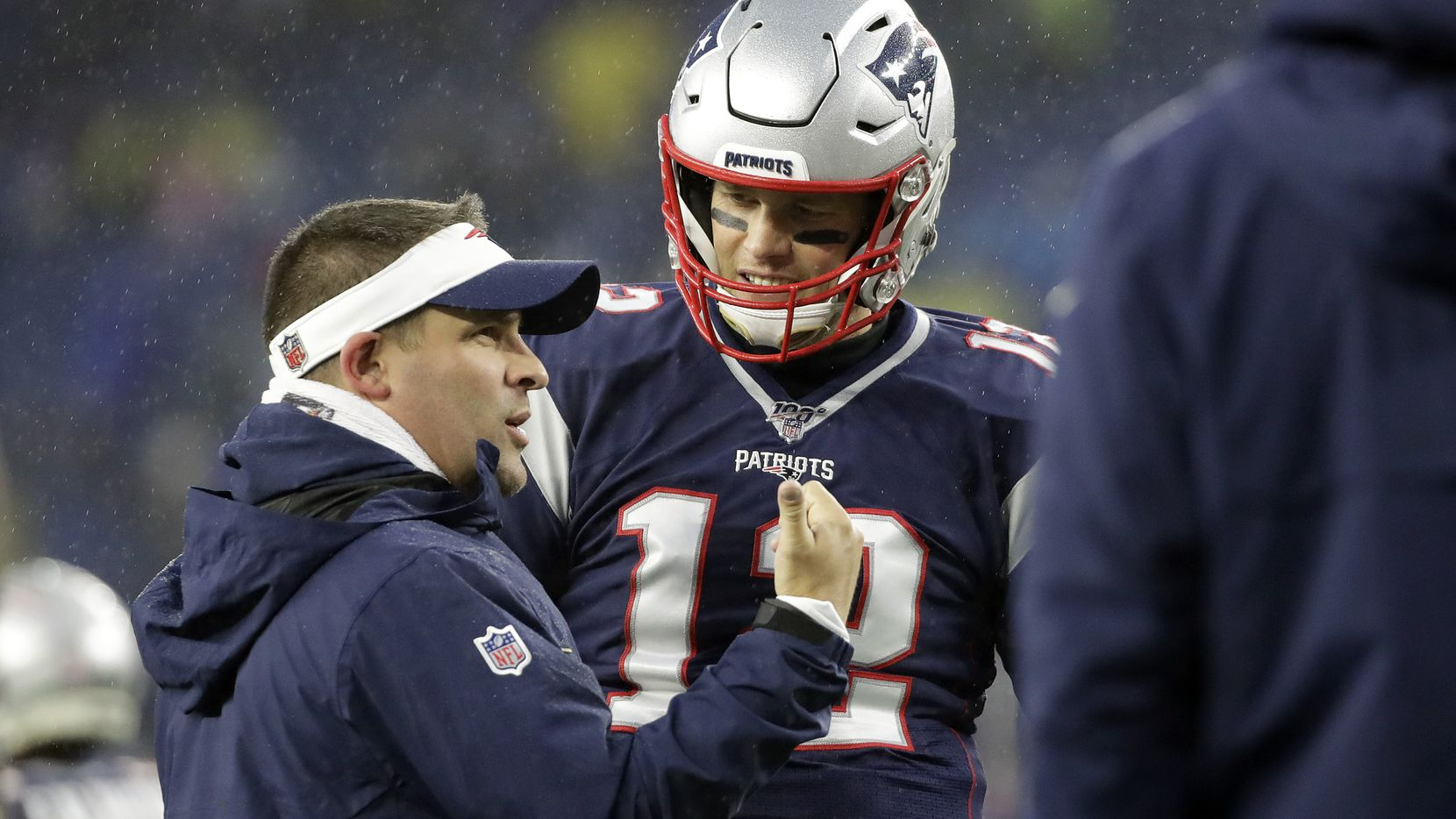 New England Patriots offensive coordinator Josh McDaniels, left, speaks to quarterback Tom Brady as the team warms up before an NFL football game against the Dallas Cowboys, Sunday, Nov. 24, 2019, in Foxborough, Mass.