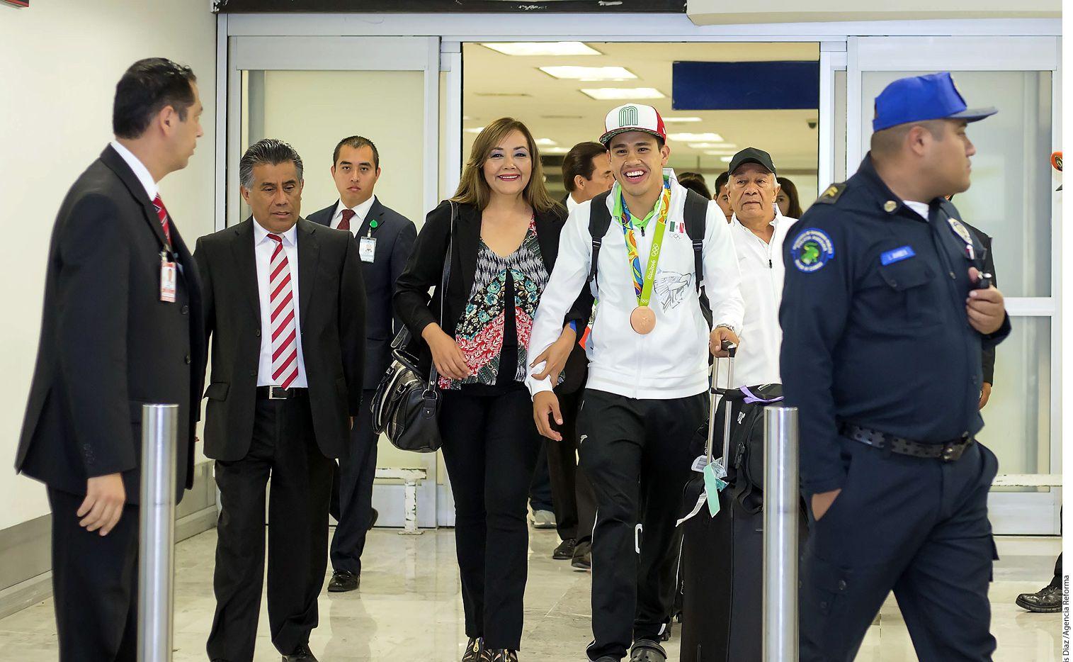 Resguardado por elementos de Seguridad Pública de la Ciudad de México, el boxeador mexicano Misael Rodríguez (der.) regresó a su país el lunes. AGENCIA REFORMA