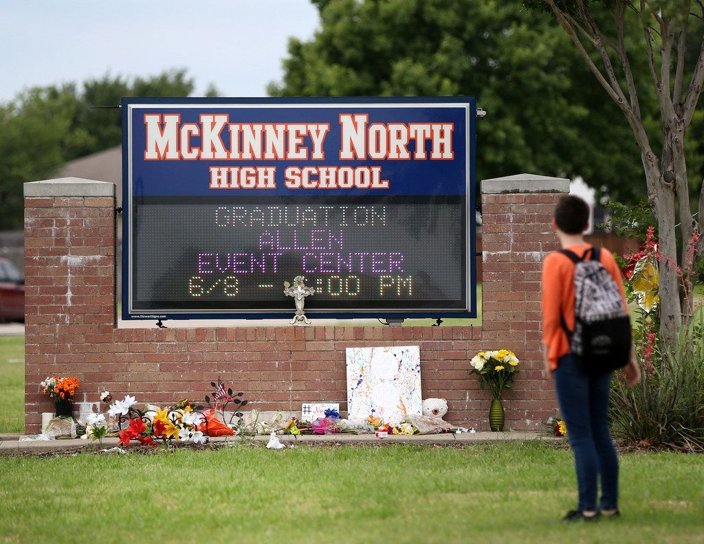 A McKinney North High School student stopped to look at a makeshift memorial while leaving the school after dismissal Monday.
