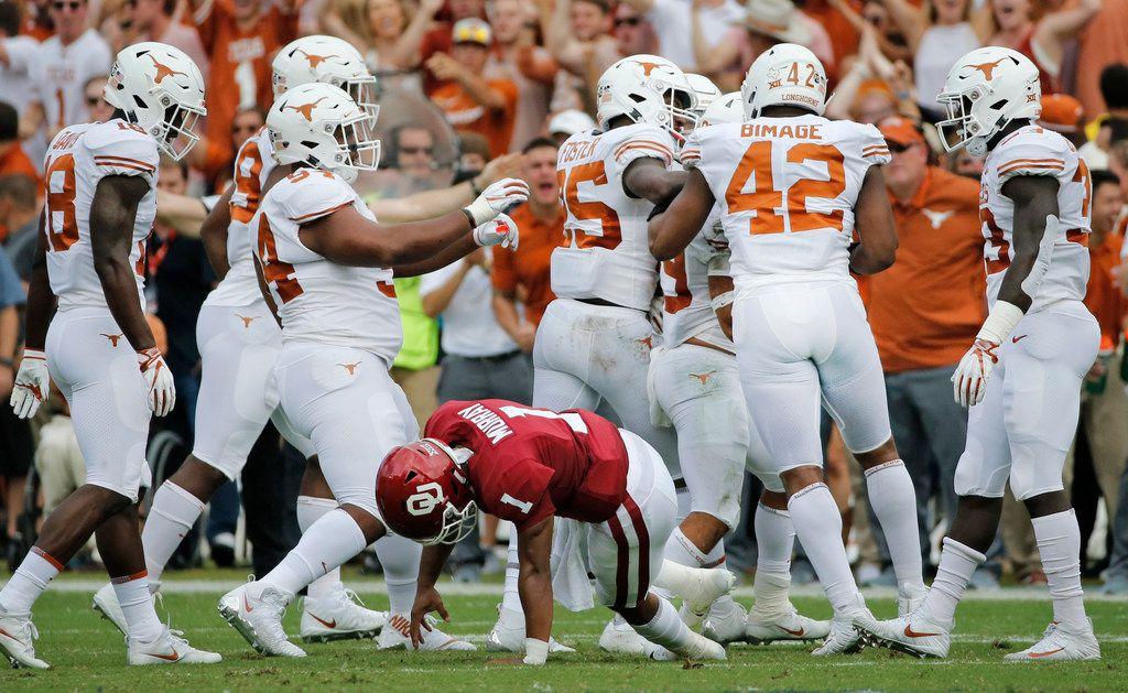 FILE - Oklahoma quarterback Kyler Murray (1) gets up slowly off the turf as the Texas defense celebrates a first-quarter interception during the University of Texas Longhorns vs. the Oklahoma Sooners NCAA football game at the Cotton Bowl in Dallas on Saturday, October 6, 2018. (Louis DeLuca/The Dallas Morning News)