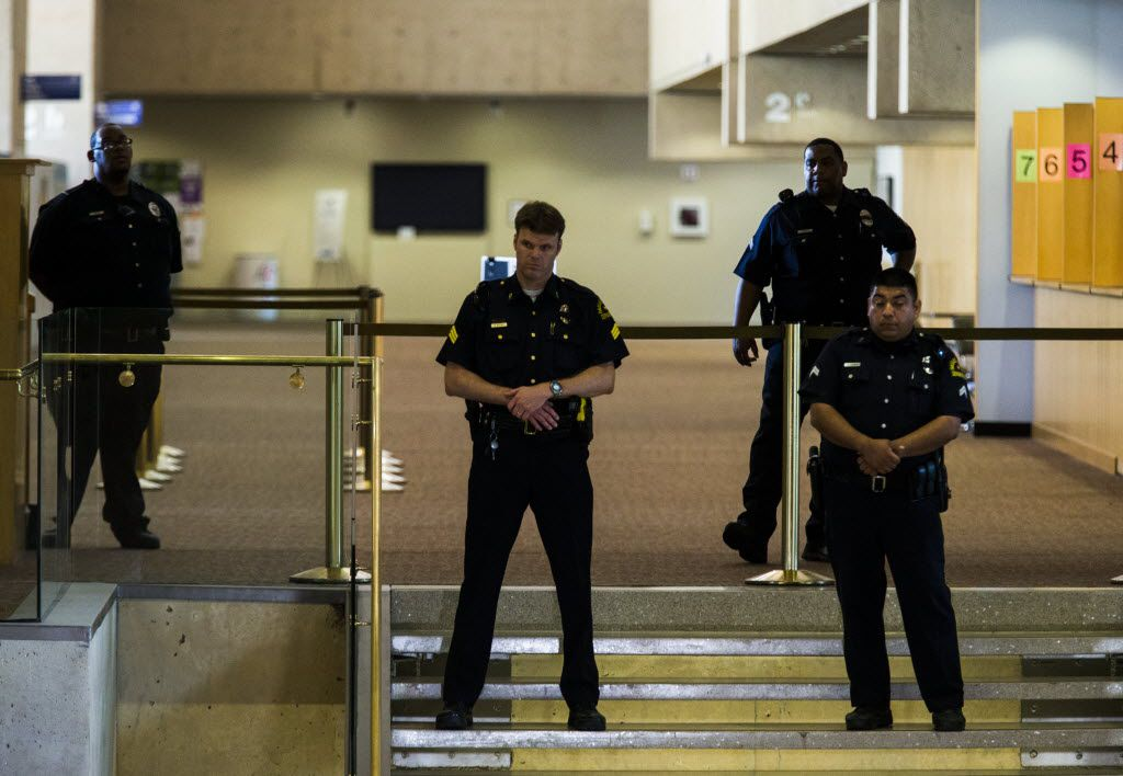 Dallas police officers watch from the top of the lobby stairs as Texas Governor Greg Abbott and Dallas Mayor Mike Rawlings speak during a press conference on Friday, July 8, 2017 at Dallas City Hall in downtown Dallas, Texas. They made comments about a shooting on Thursday, July 7, 2016 in downtown Dallas that targeted police officers and left five people dead and seven more injured. (Ashley Landis/The Dallas Morning News)