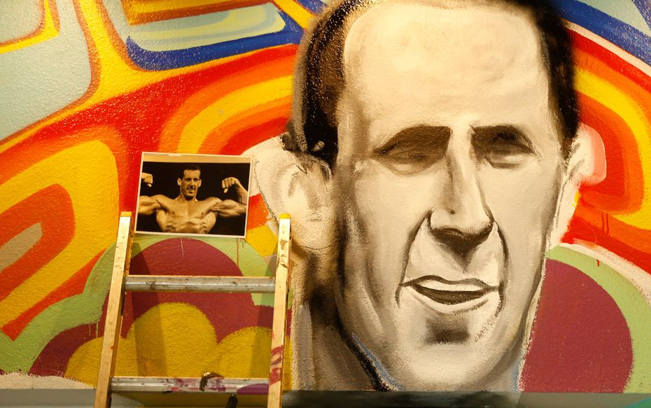 A photograph of Larry North is used to paint his likeness on a mural.  (Nathan Hunsinger/The Dallas Morning News)