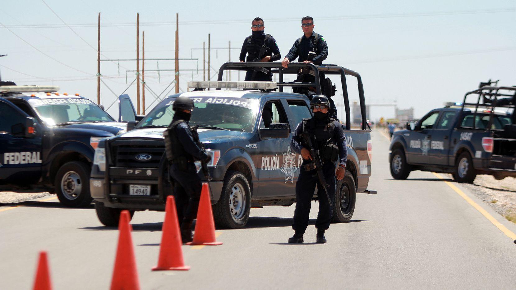 Policías federales mexicanos vigilan una carretera que conduce a la cárcel Cefereso No. 9 en Ciudad Juárez, México, el sábado 7 de mayo de 2016.