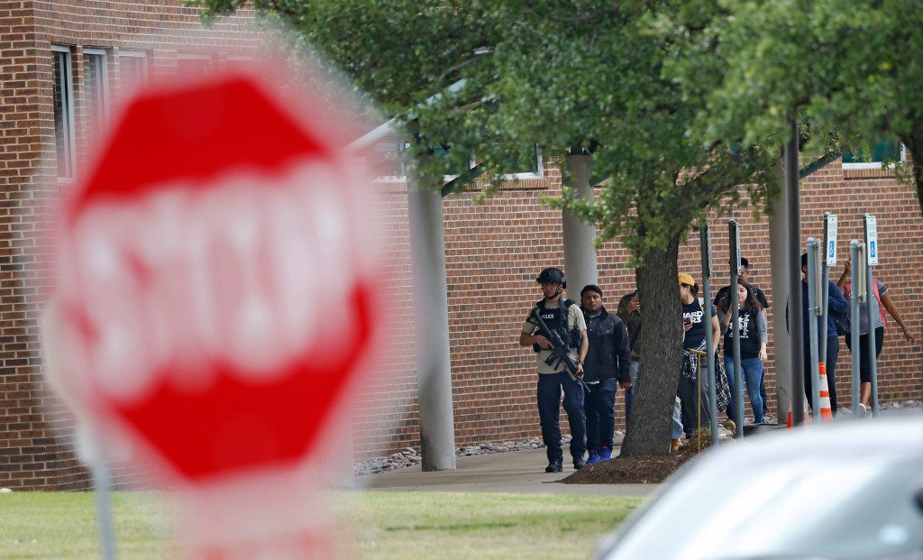 Police guide students and faculty out of a building after a shooting at North Lake College in Irving.