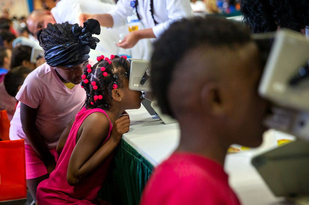 Damiyah Nelson, 6 (center), receives an eye screening during the 23rd annual Mayor's Back to School Fair at the Fair Park Centennial Hall in Dallas on Friday, Aug. 2, 2019. Thousands of children and their family members were expected to attend, and the event included health and eye screenings, dental screenings, backpack giveaways and more.