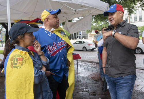 Jennifer Zabala (izq.) y su esposo Honorio llegaron a la protesta en Ferris Plaza pese a la intensa lluvia del domingo. KYE LEE/DMN