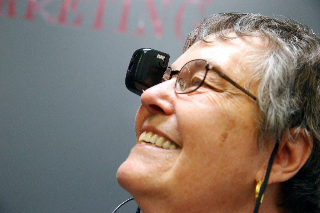 Ana Russo wears a seeBOOST, a camera that allows her to see far distances, in the call center at Bold Sales Solutions, a subsidiary of Dallas Lighthouse for the Blind.