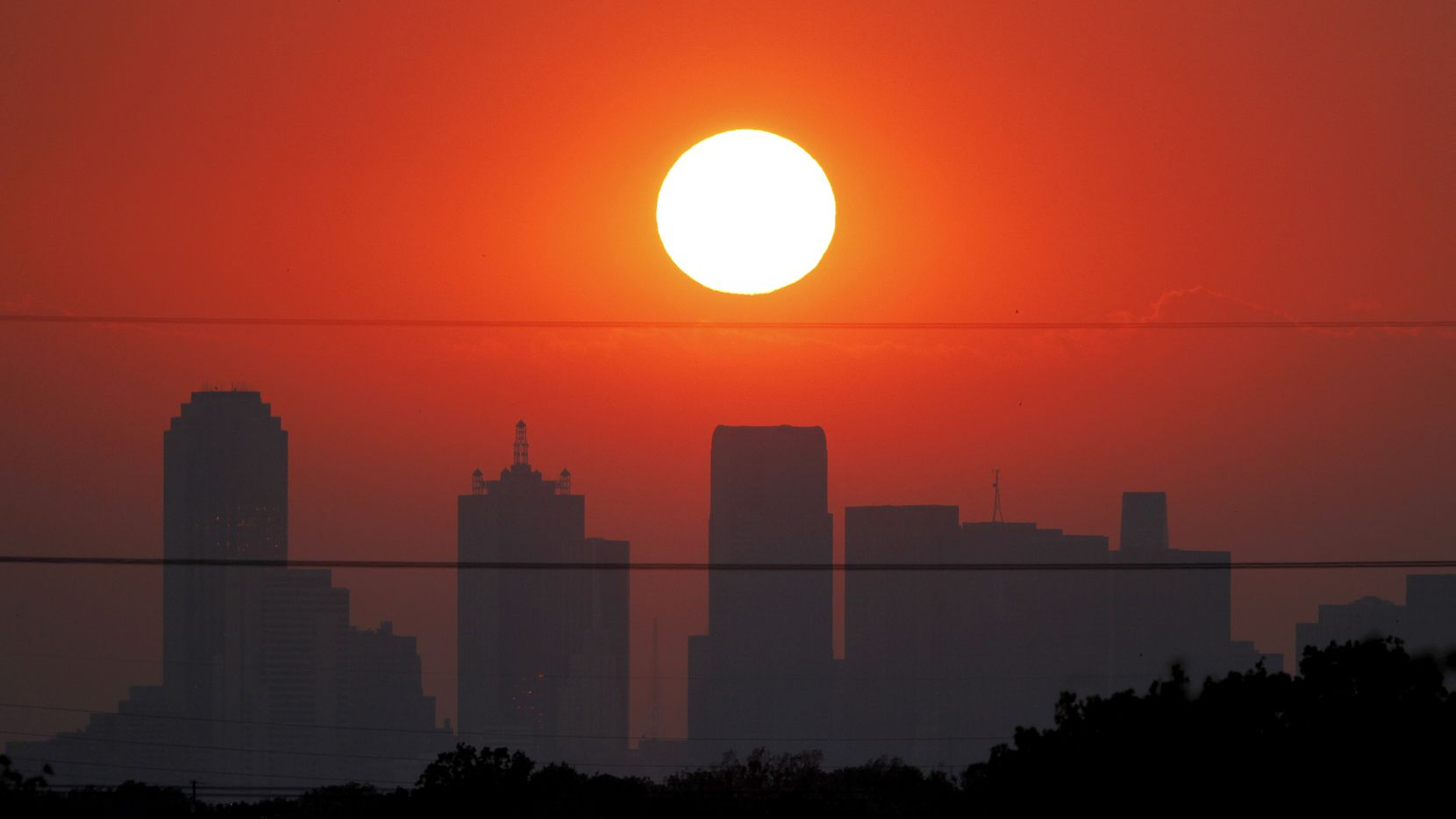 The sun sets beyond a humid city skyline following the storm that passed through Dallas, Texas.