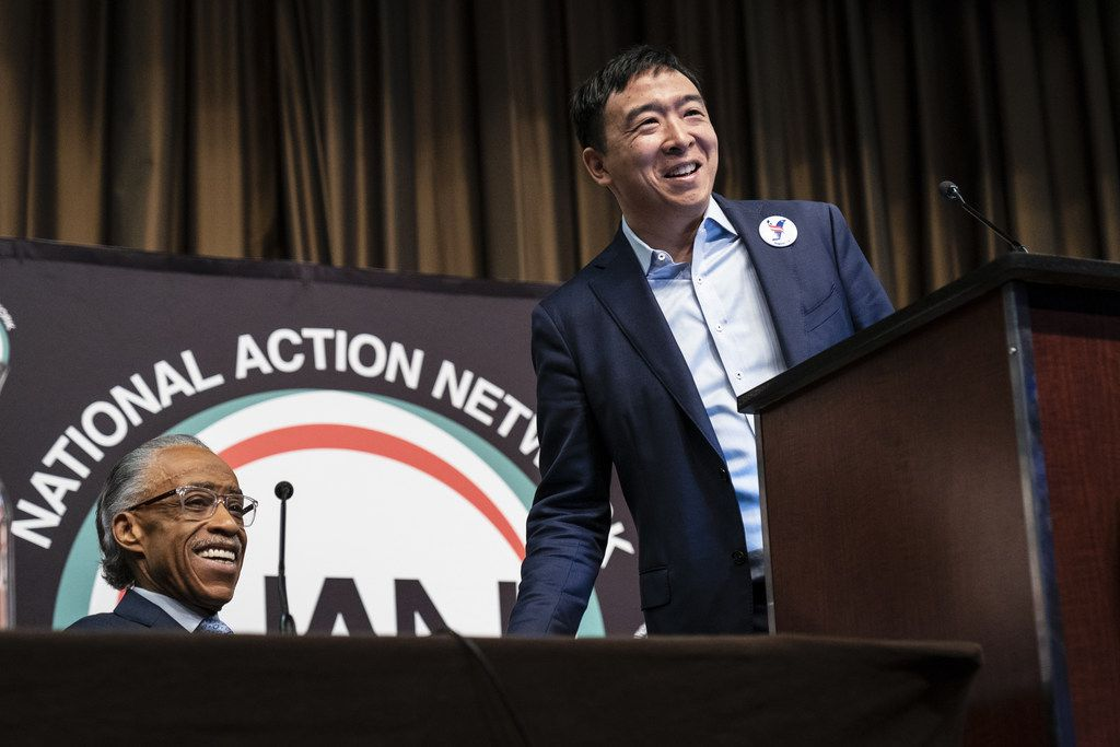 The Rev. Al Sharpton looks on as entrepreneur and Democratic presidential candidate Andrew Yang speaks at the National Action Network's annual convention in New York City. A dozen 2020 Democratic presidential candidates will speak at the organization's convention this week.