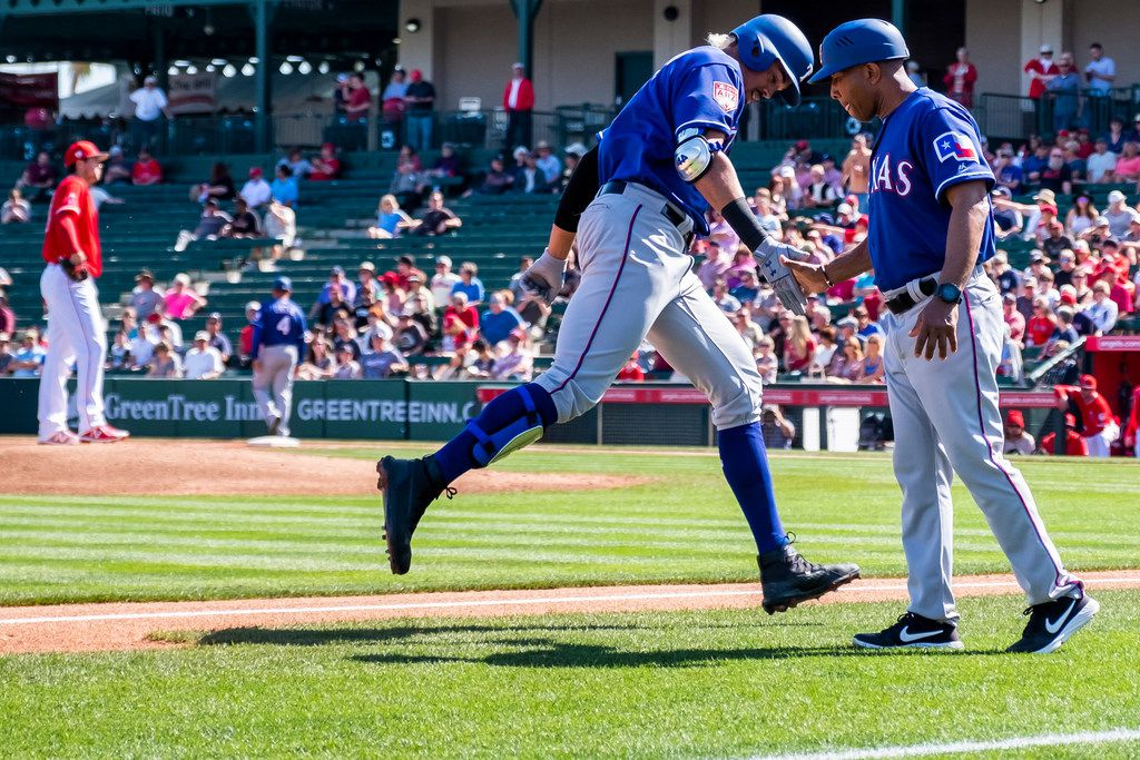 Rangers first baseman Ronald Guzman slaps hands with third base coach Tony Beasley as he rounds the bases following a solo home run off of Los Angeles Angels pitcher Tyler Skaggs (left) — his first of two on the day — during the second inning of a spring training game on  Feb. 28 in Tempe, Ariz.
