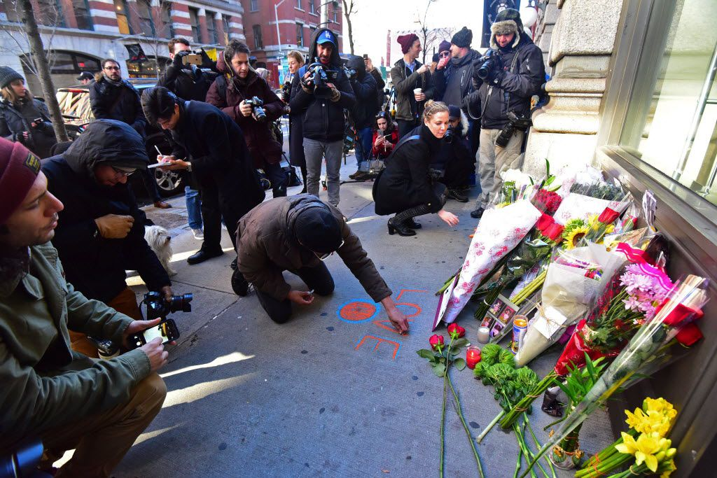 """People leave flowers and messages outside the residence of British music legend David Bowie, on January 11, 2016, in New York. Bowie has died at the age of 69 after a battle with cancer, drawing an outpouring of tributes for one of the most influential and innovative artists of all time. A notoriously private person, Bowie's death came as a shock for the world just days after he had released his 25th studio album """"Blackstar"""" on his 69th birthday on January 8. """"David Bowie died peacefully today (Sunday) surrounded by his family after a courageous 18 month battle with cancer,"""" said a statement posted on his official social media accounts on January 11."""