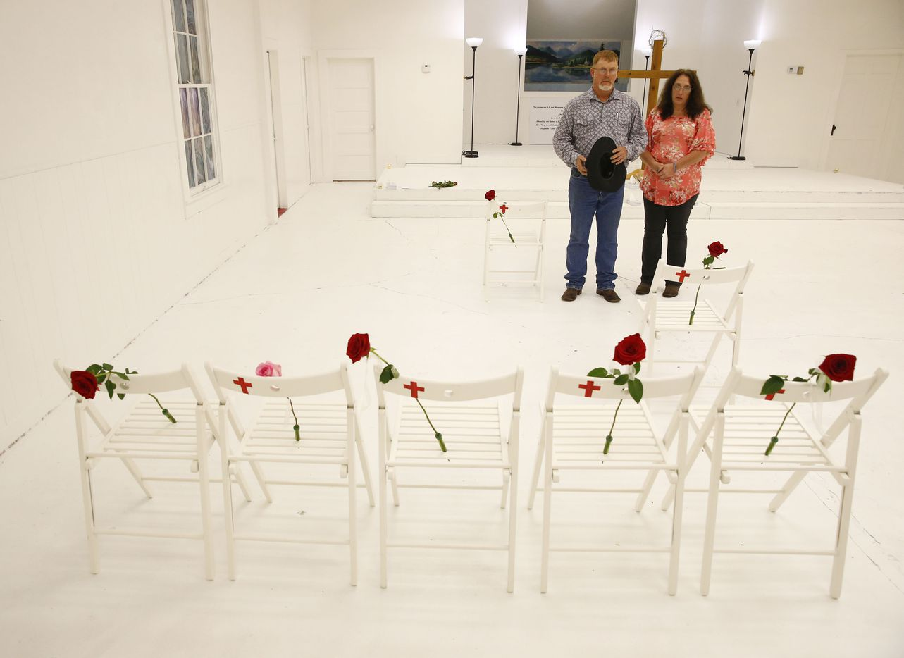 Robert Kunz and his wife Lisa Kunz look at chairs and roses representing the slain as visitors are allowed into First Baptist Church to pay their respects a week after the shooting in Sutherland Springs, Texas on Nov. 12, 2017. The church was the site of a shooting that killed 26 and left 30 injured.