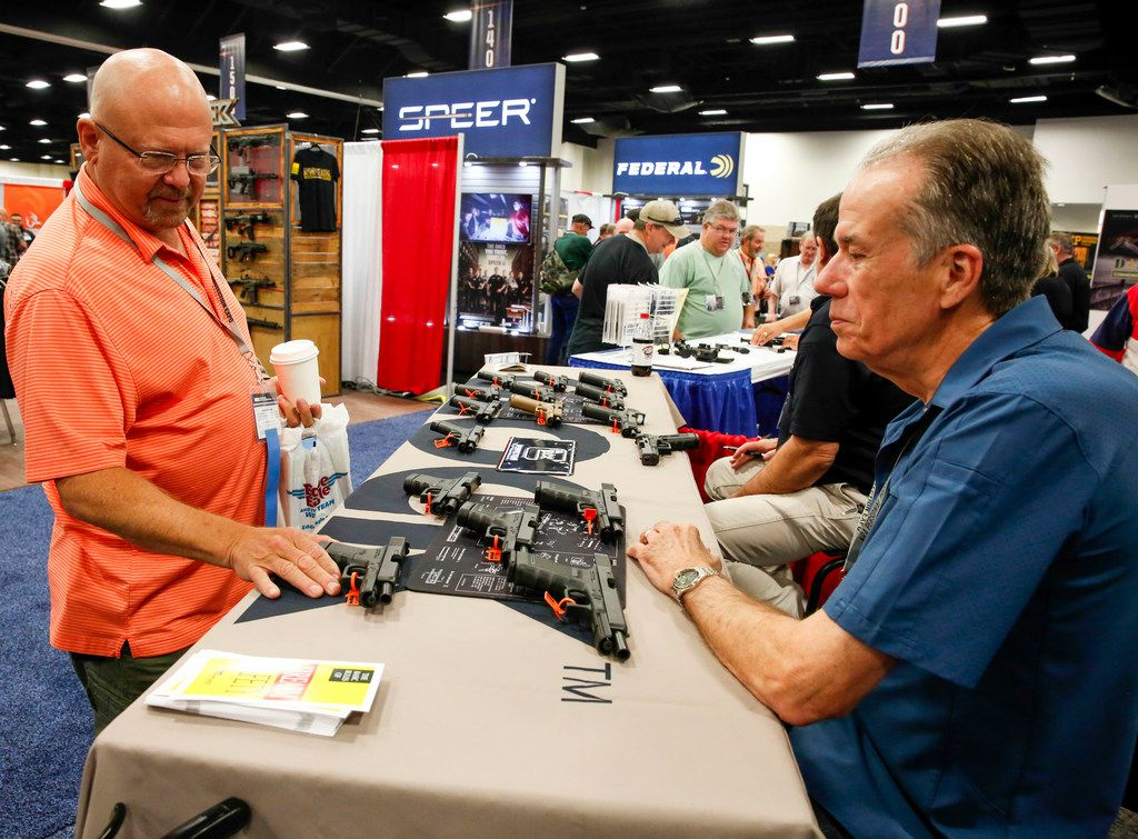 Sandy Evans of Arlington talks to Glock vendor Warren Ackerson at the Fort Worth expo.