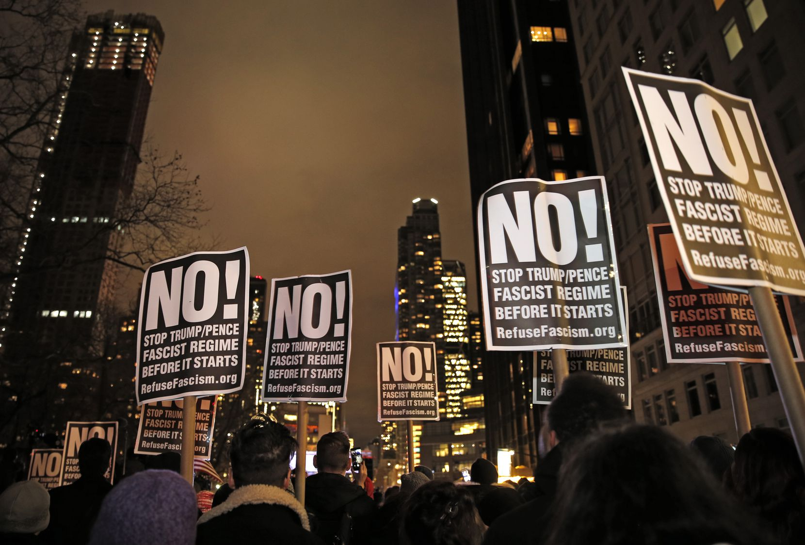 Protesters hold signs as they listen to speakers at an anti-Trump rally hosted by filmmaker Michael Moore in front of the Trump International Hotel, Thursday, Jan. 19, 2017, in New York. President-elect Donald Trump, a New Yorker, is scheduled to take the oath of office Friday in Washington.