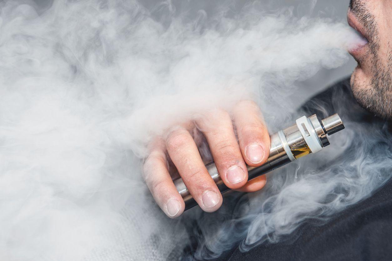 Una persona fumando de un cigarrillo electrónico.