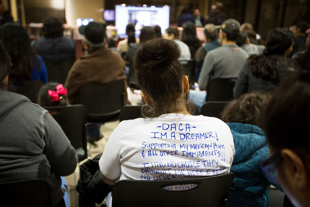 """A woman wears a shirt identifying herself as a """"Dreamer"""" - people effected by the Deferred Action for Childhood Arrivals program - as an overflow crowd spills out into the next room to watch on a television monitor during a community meeting on possible deportations at the Consulate General of Mexico on Thursday, Feb. 16, 2017, in Dallas. (Smiley N. Pool/The Dallas Morning News)"""
