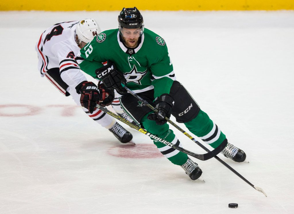 Dallas Stars center Radek Faksa (12) keeps control of the puck ahead of Chicago Blackhawks center David Kampf (64) during the first period of an NHL game between the Dallas Stars and the Chicago Blackhawks on Thursday, December 20, 2018 at American Airlines Center in Dallas. (Ashley Landis/The Dallas Morning News)