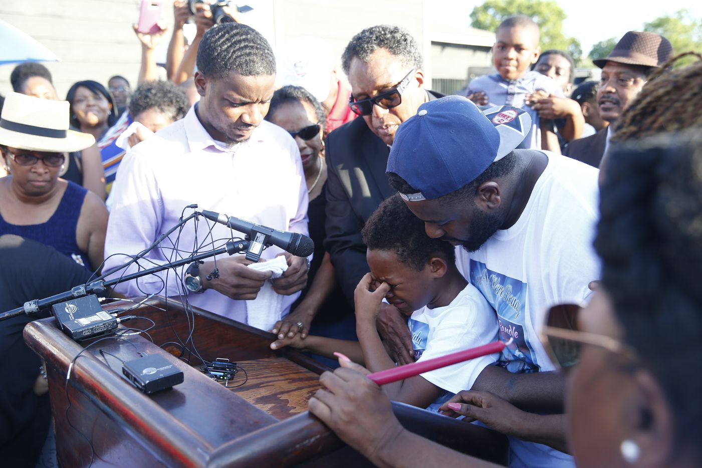 "C.J. Randle, 11, brother of Shavon Randle, is lifted up to the podium to say ""She didn't do anything,"" before being taken over by emotion during Monday's vigil."