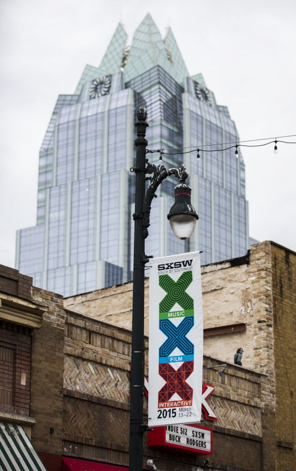 A SXSW festival sign is posted on a light pole beneath the iconic Frost building.
