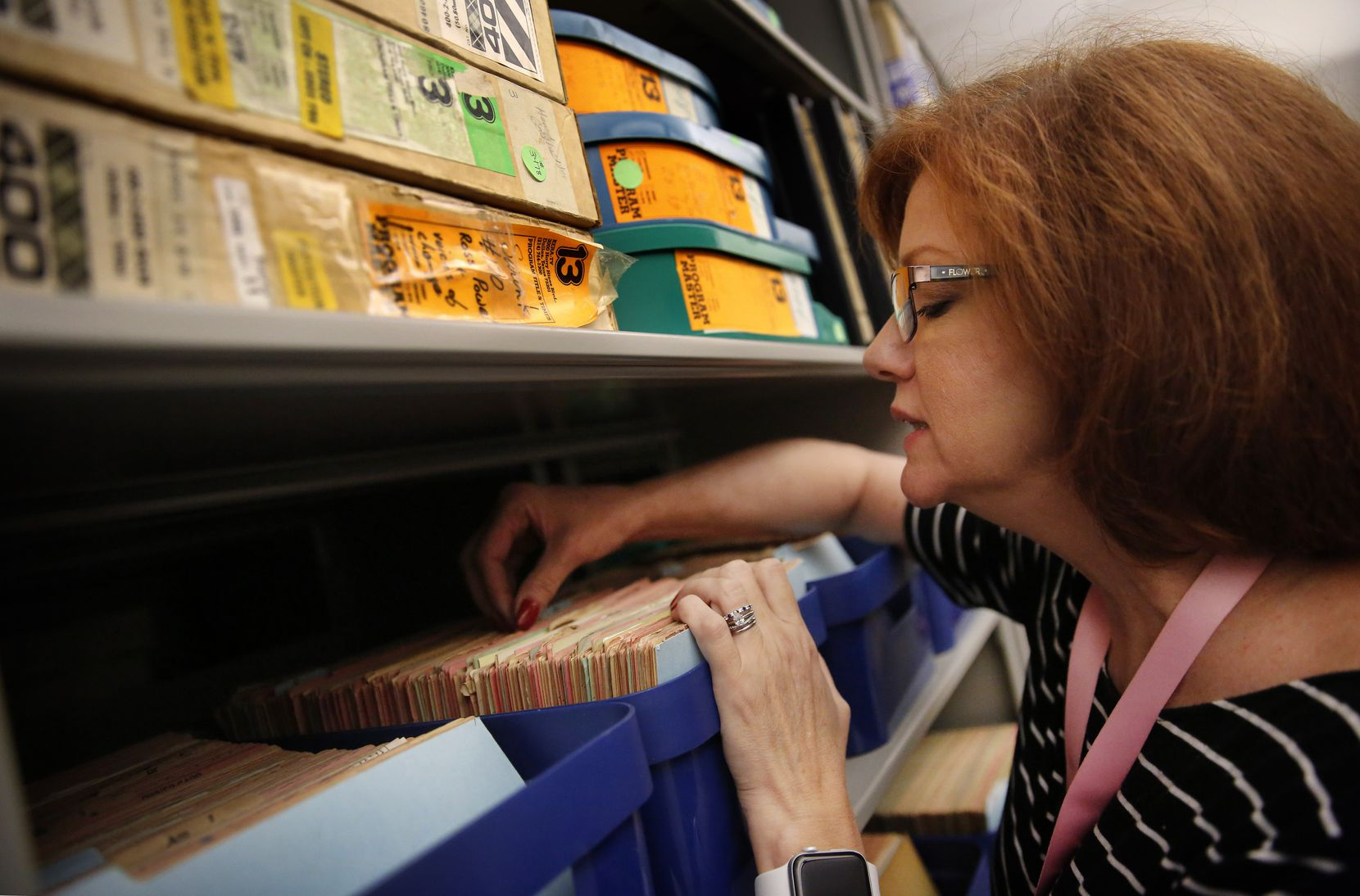 Christine Sharbrough, manager of the library's Dallas History & Archives Division, looks through lot owners cards as part of the Oakland Cemetery records collection.