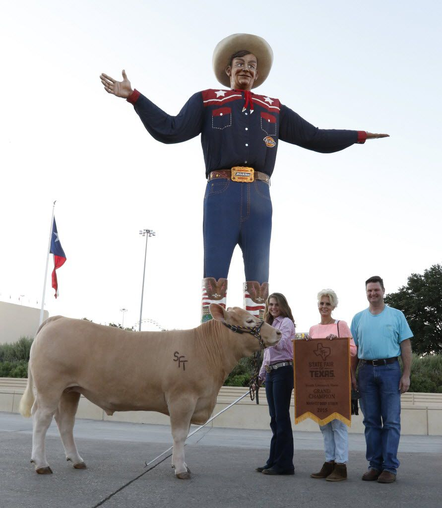 Laurel Kelley, 15, left, posed Thursday with her Grand Champion Steer, RFD, in front of Big Tex along with her parents, Jennifer and Tom Kelley from Yoakum. The steer will be auctioned today and could be sold for more than $100,000.