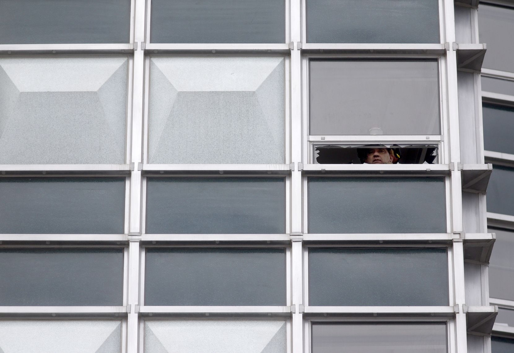 A Dallas Fire-Rescue captain is seen through a broken window on the 16th floor of the Statler Dallas residences, that DFR smashed to ventilate the room.