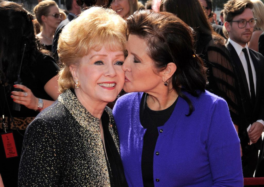 "Debbie Reynolds (left) and Carrie Fisher arrive at the Primetime Creative Arts Emmy Awards in Los Angeles. Reynolds, star of the 1952 classic ""Singin' in the Rain"" died Wednesday, according to her son Todd Fisher. She was 84. (2011 File Photo/The Associated Press)"