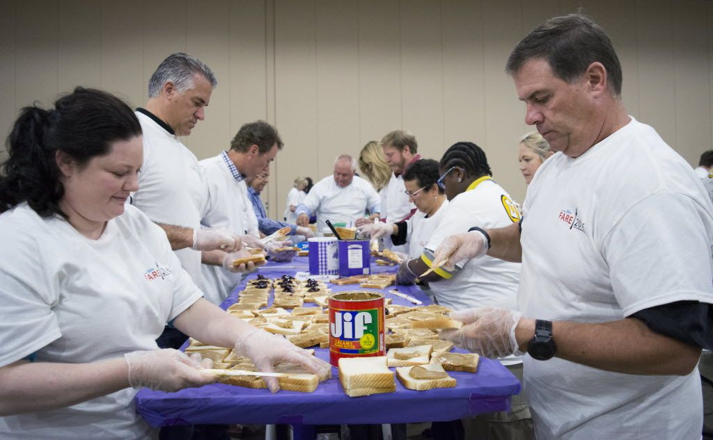 Spread the Love volunteer Dan Schneider works with his team to finish as many PB&J sandwiches before the one hour time limit is up.
