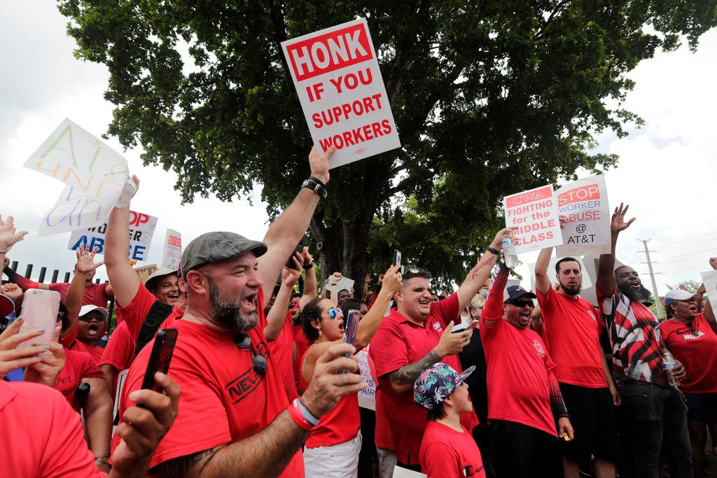 Members of the Communications Workers of America shouted Monday as they walked a picket line outside of an AT&T office in Miami.