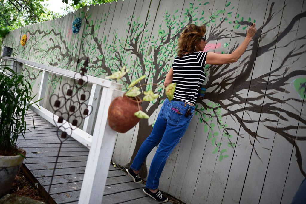 Julie Shipp, who teaches art at Collin College, volunteered to paint a tree mural on a fence at the home for patients with advanced AIDS.