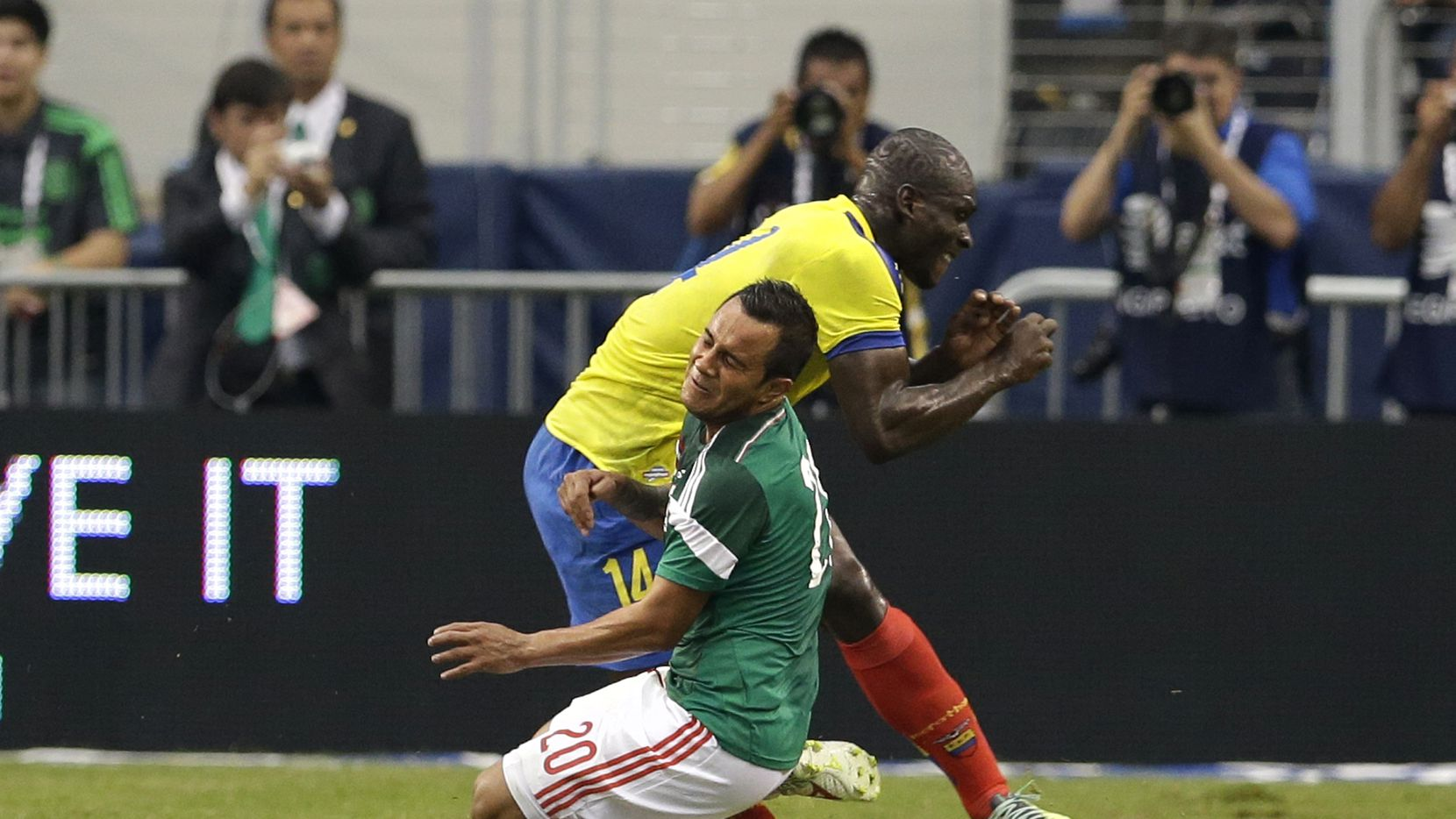 Mexico's Luis Montes collides with Ecuador's Segundo Castillo, rear, as the two were competing for the ball during the first half of a friendly soccer match, Saturday, May 31, 2014, in Arlington, Texas. Montes, who took the brunt of the collision was stretchered off the pitch after fracturing his right tibia and fibula. (AP Photo/Tony Gutierrez) 04112015xALDIA