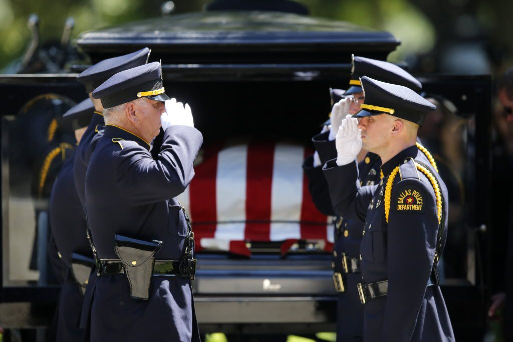 Dallas police Honor Guard members salute before removing the flag-draped casket of slain Dallas police Sgt. Michael Smith  from the horse-drawn caisson.  Smith was laid to rest at the Restland Funeral Home and Cemetery in Dallas, Thursday, July 14, 2016. Smith was gunned down in an ambush attack in downtown Dallas a week ago. Four Dallas police officers and one DART officer were killed. (Tom Fox/The Dallas Morning News)