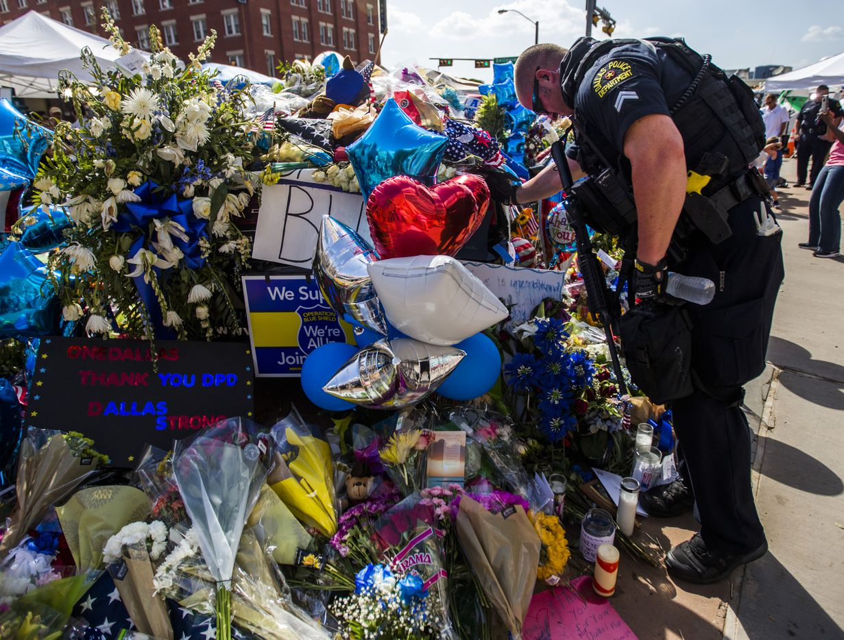 Senior Corporal Daniel Sullivan leans on a squad car surrounded with flowers and messages of support on July 10, 2016, outside Dallas police headquarters. (Ashley Landis/Staff Photographer)