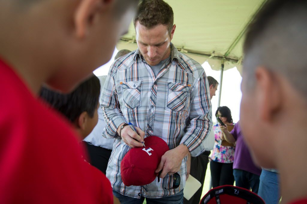 """Rangers outfielder Josh Hamilton signs autographs for kids involved in the Mercy Street West Dallas program during the unveiling of the Josh """"Hambone"""" Hamilton Field at the  Texas Rangers Youth Academy Mercy Street Sports Complex on July 28, 2016 in Dallas. (Ting Shen/The Dallas Morning News)"""