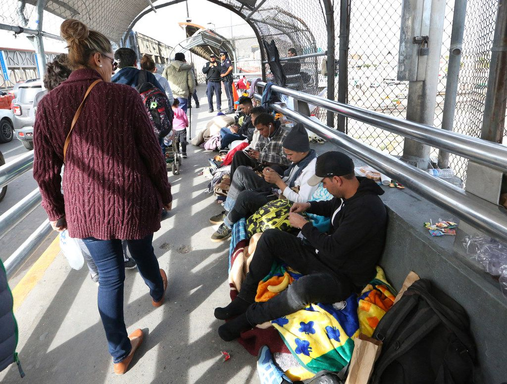 Documented border crossers walk past a group of undocumented migrants waiting to enter the U.S. atop the Paso Del Norte international Bridge between El Paso and Juarez, Mexico on Nov. 1, 2018. Just over 100 migrants were camped out at the bridge waiting to enter the U.S.