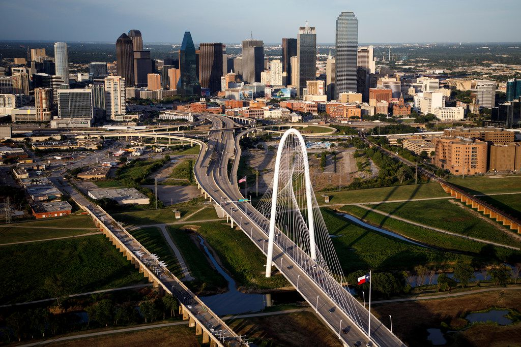 The downtown skyline and Margaret Hunt Hill Bridge photographed on Thursday, July 27, 2017, in Dallas. (Smiley N. Pool/The Dallas Morning News)  EDS NOTE -- CAPTION INFO ADDED WITH NEW INFORMATION AS OF 1/31/18 -- A new waterfront development in the works near downtown Dallas would bring housing, retail and commercial buildings to the banks of the Trinity River. Developers Forest City Realty and Trademark Property are teaming up on the mixed-use development proposed on Riverfront Boulevard at the Margaret Hunt Hill Bridge. The roughly 42-acre building site is on both sides of the bridge along the banks of the river, at 505 Riverfront Boulevard, shown here (at center) in the empty lots adjacent to the highway.