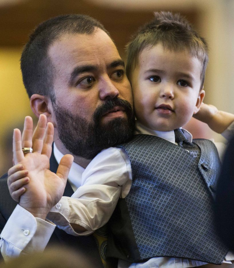 State Rep. Joe Moody is sworn in while holding his son, William Moody, 2, during the first day of the 85th Texas Legislative Session on Tuesday at the Texas State Capitol in Austin.