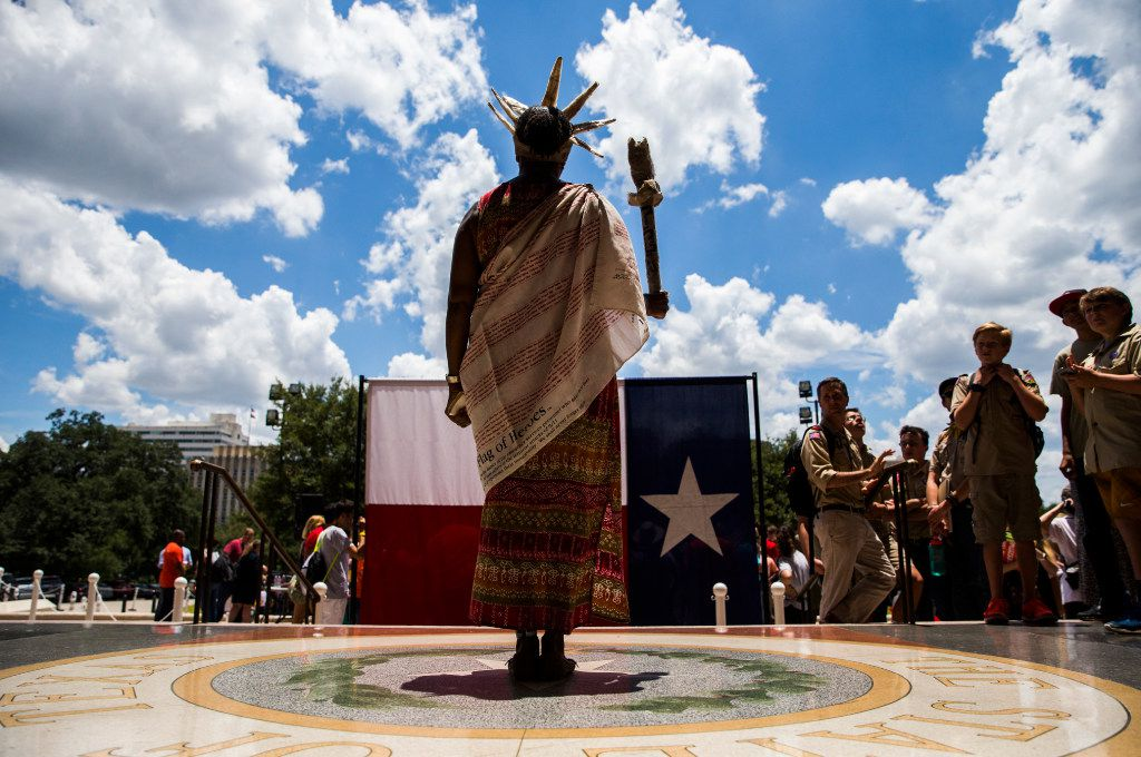 Peace Washington stands dressed as the statue of liberty behind a Texas flag near a One Texas Resistance rally on the south steps of the capitol on the first day of a legislative special session on Tuesday, July 18, 2017 at the Texas state capitol in Austin, Texas. (Ashley Landis/The Dallas Morning News)