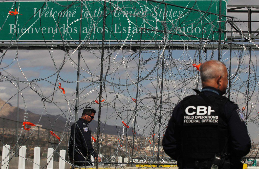 Members of the border patrol look by barbed-wire barriers that are being installed at the Zaragoza International Bridge on the US-Mexico border as seen from Ciudad Juarez, Chihuahua State, Mexico, on February 22, 2019.