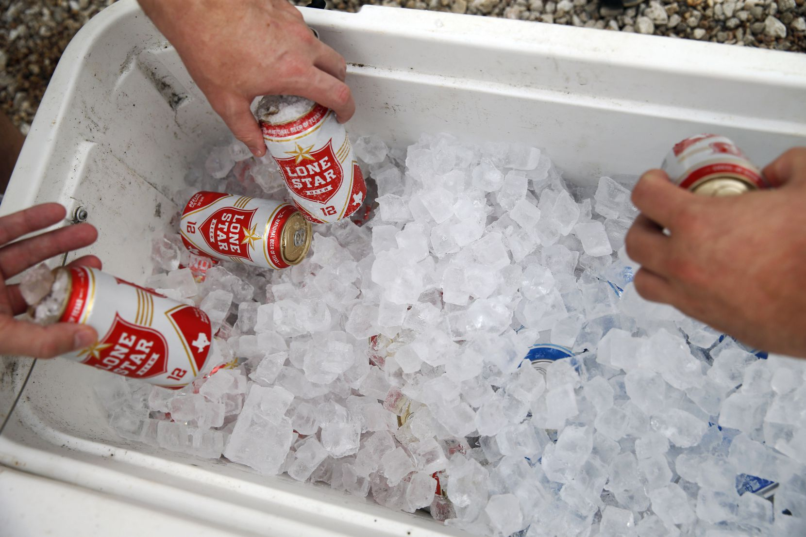 People grab free beer to drink as they wait in line at Snow's BBQ.