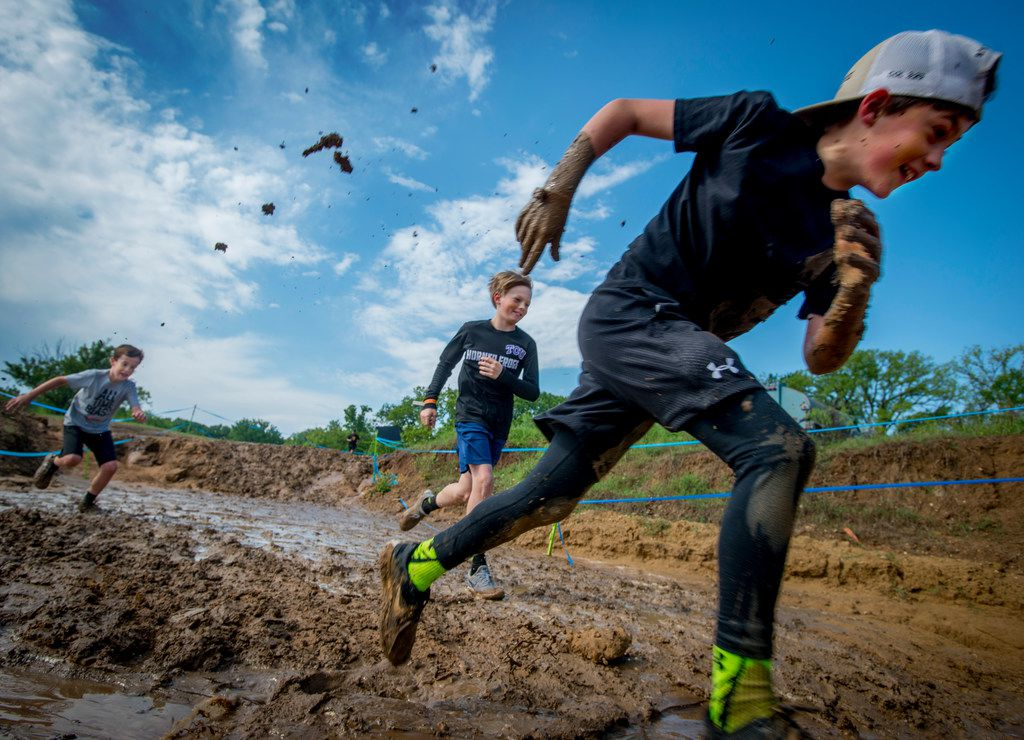 Kids run through the mud during the Kids Obstacle Challenge at Village Creek Motocross Park in Fort Worth.
