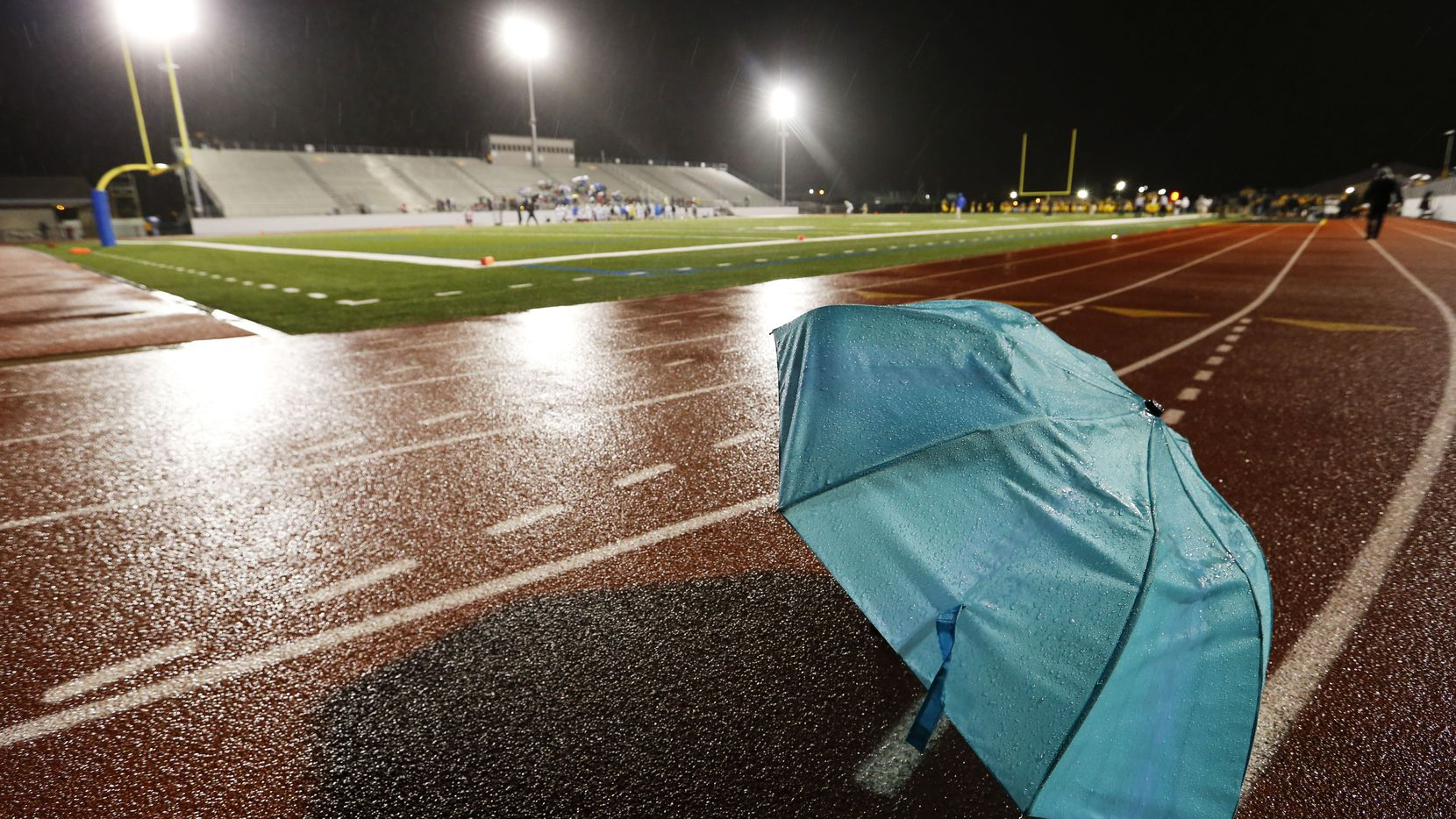 An umbrella rests on the track shortly before the start of the Garland and Garland Lakeview high school football game at Williams Stadium in Garland, on Oct. 22, 2015. (Vernon Bryant/The Dallas Morning News)