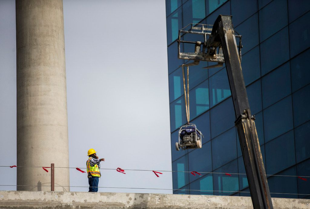 A construction worker guides a forklift holding equipment to the second level of the front entrance of the future site of Toyota world headquarters on Thursday, October 13, 2016 in Plano, Texas. (Ashley Landis/The Dallas Morning News)