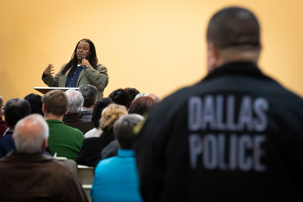 """A Dallas Police officer listens as Walter """"Changa"""" Higgins addresses a Citizens Police Review Board town hall meeting at Highland Oaks Church of Christ in January."""