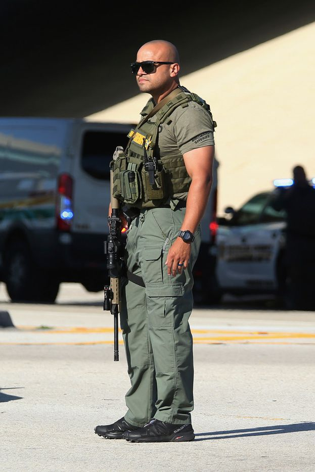 A member of the Broward County Sheriff's Office stand watch at the site of a shooting at Marjory Stoneman Douglas High School in Parkland, Fla., Wednesday, Feb. 14, 2018. A shooter opened fire at the Florida high school Wednesday, killing people, sending students running out into the streets and SWAT team members swarming in before authorities took the shooter into custody. (AP Photo/Joel Auerbach)