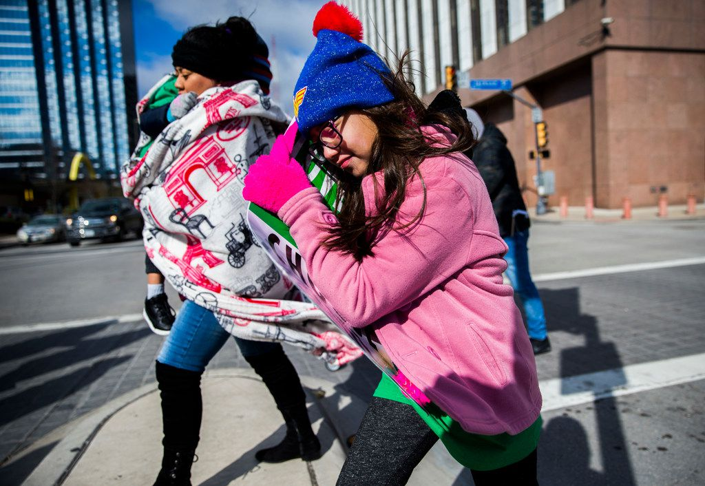 Krystal Alba, 9, shields her face from the wind as she and her family cross South Griffin Street on Saturday, Jan. 19, 2019, in downtown Dallas. Temperatures dropped 30 degrees over night and winds gust up to 40 mph.